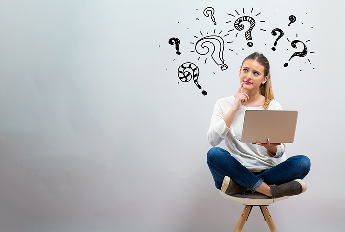 Question marks with young woman using her laptop